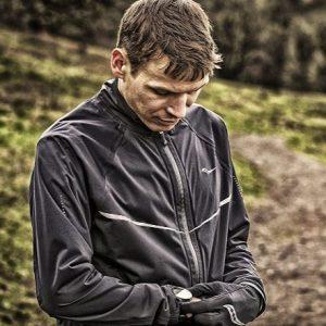 Hombre en una ruta de montaña mirando su reloj deportivo