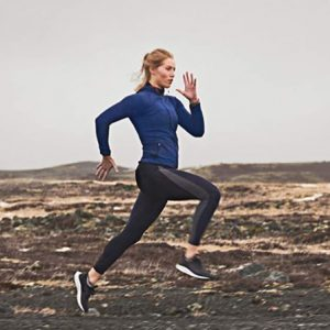 Mujer corriendo en una montaña con un garmin